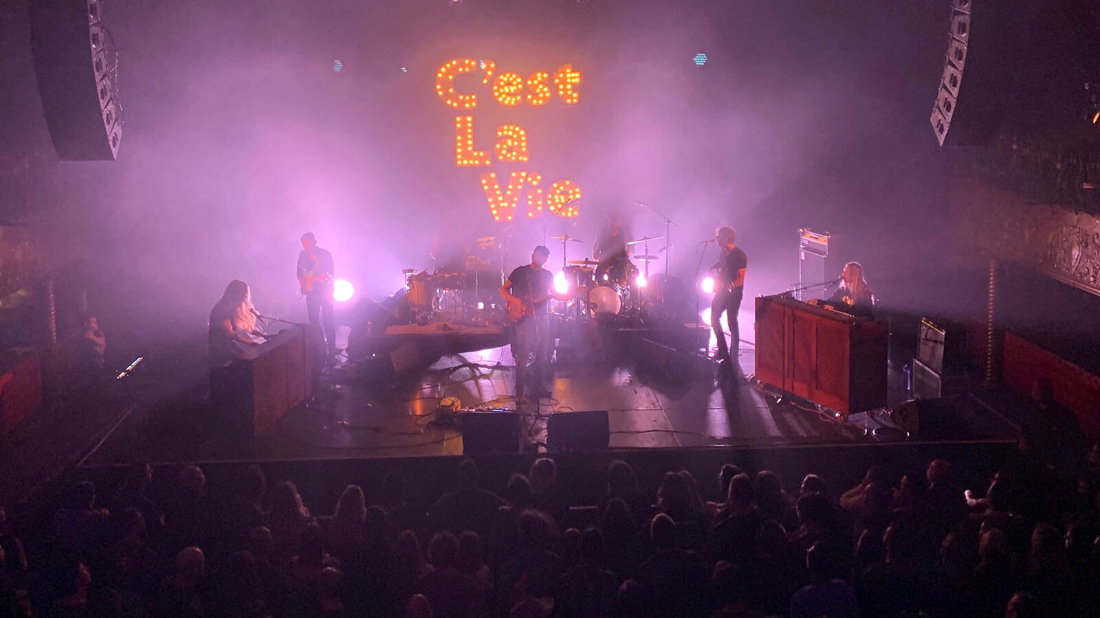 Phosphorescent (Matthew Houck) and his six-piece band perform on stage before a crowd. The lighting is tinted purple and the band is backed by a large, illuminated sign reading 'C'est La Vie', the title of their recent album.